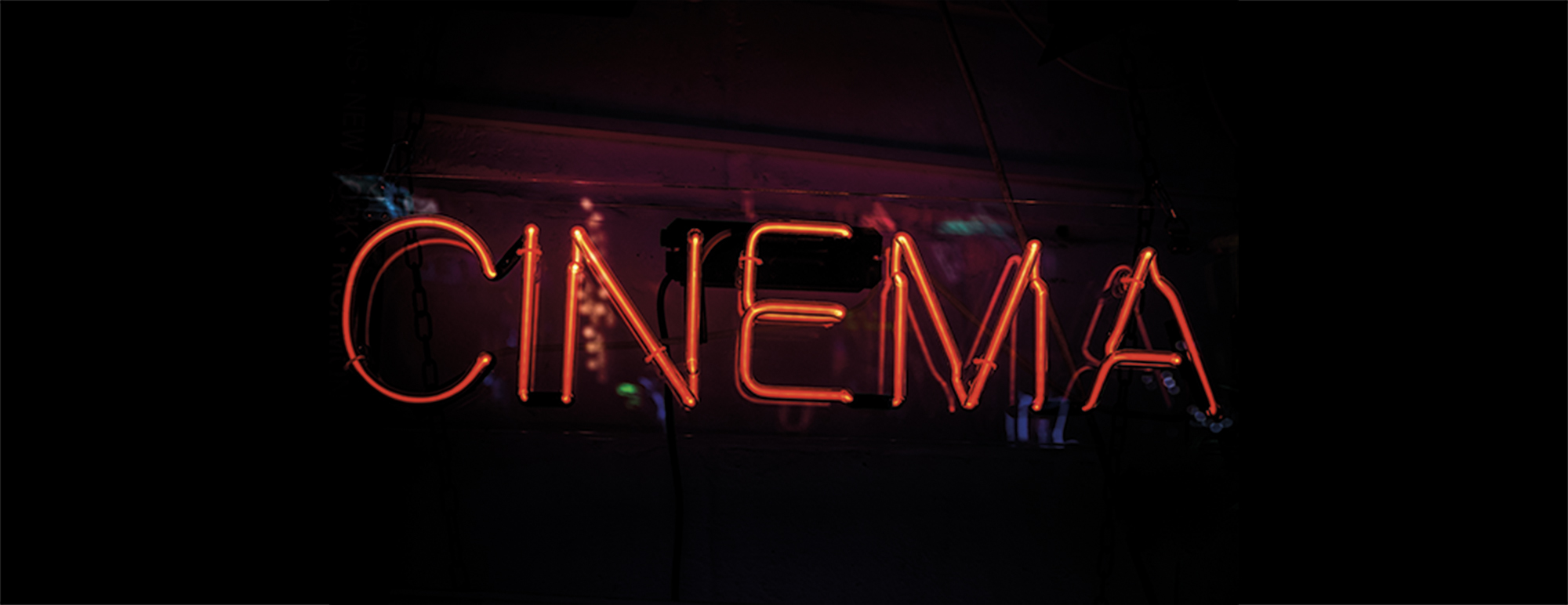 Glowing red sign saying 'cinema', horizontal with plenty of copy space.